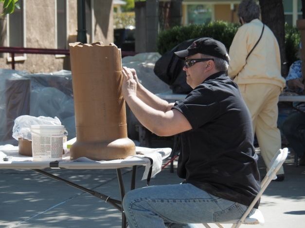 Art League of Lincoln's Art Center Director, John Robeck, works in the sun at the Clay Day event.
